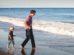 Ensamstående pappa med sitt barn på en strand